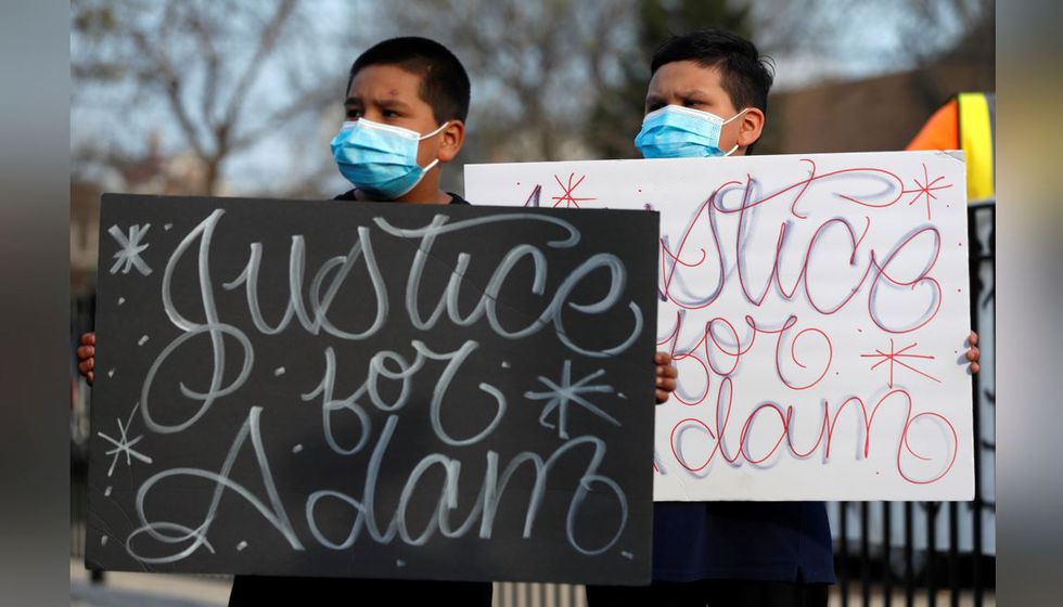 FILE - In this Tuesday, April 6, 2021 file photo, Jacob Perea, 7, left, and Juan Perea, 9, hold...
