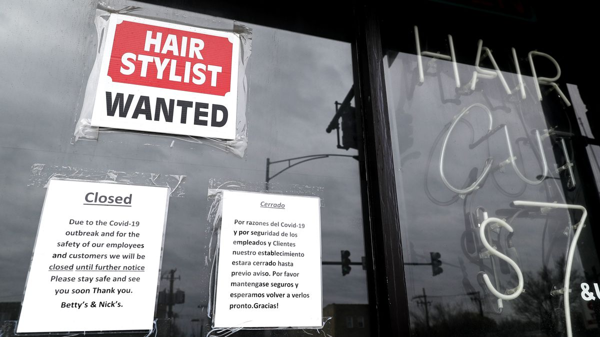 In this April 30 ,2020 file photo, a barber shop shows closed and hiring sign during the...