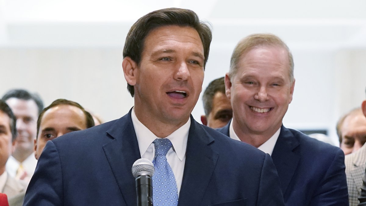 FILE - In this April 30, 2021, file photo surrounded by lawmakers, Florida Gov. Ron DeSantis...