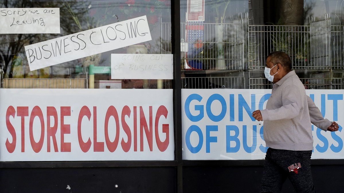 A man looks at signs of a closed store due to COVID-19 in Niles, Ill., Thursday, May 21, 2020....