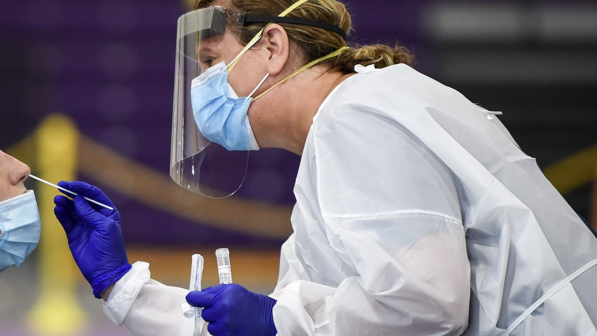 A nurse takes a swab from a patient during a COVID-19 mass testing event at Minnesota State...