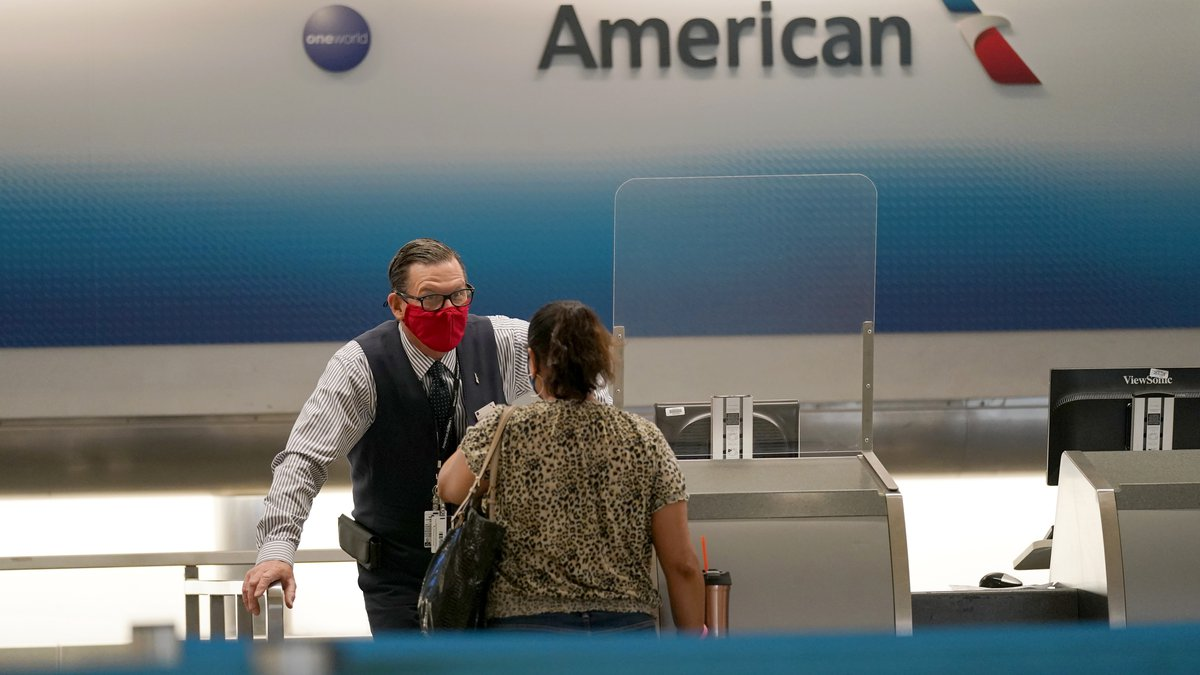 American Airlines ticket agent Henry Gemdron, left, works with a customer at Miami...