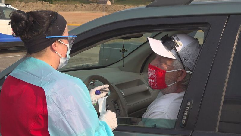 A South Dakota health care workers administers a drive-thru COVID-19 test.