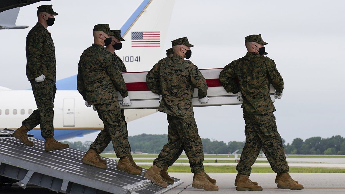 A carry team moves a transfer case containing the remains of Marine Corps Lance Cpl. Jared M....