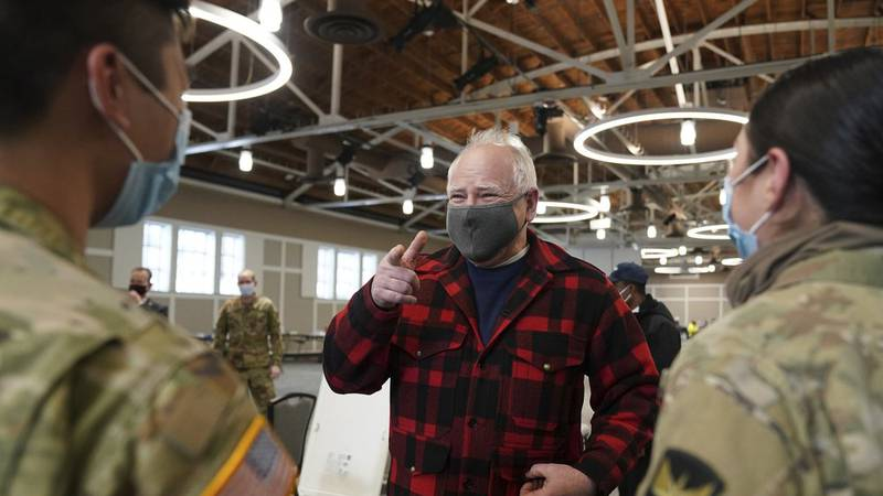 Gov. Tim Walz talks with members of the National Guard who were helping manage the people there...