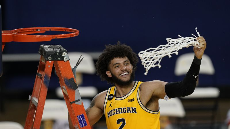 Michigan forward Isaiah Livers twirls the net after the team won the Big Ten title against...