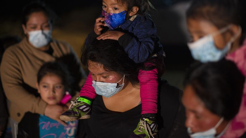 Migrant families coming from Guatemala, wait at a U.S. Border Patrol intake site after they...