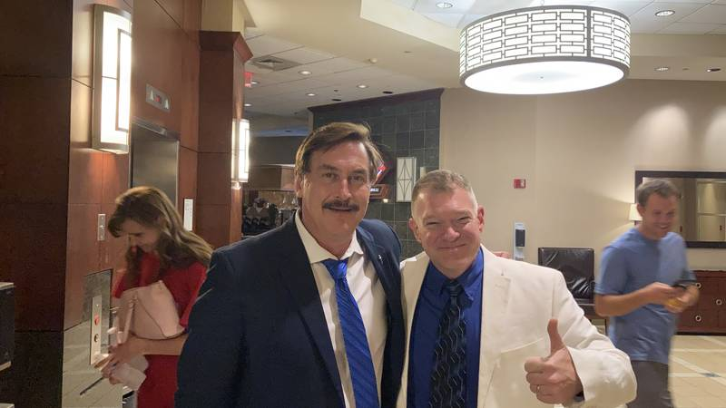 Major Ryan Kelly has his photo taken with Mike Lindell on August 11, 2021.  The following day...