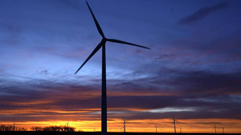 FILE - In this Jan. 13, 2021, file photo, wind turbines are silhouetted against the sky at dawn...