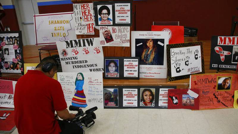 FILE - In this June 14, 2019, file photo, a photographer videos signs in memory of missing and...