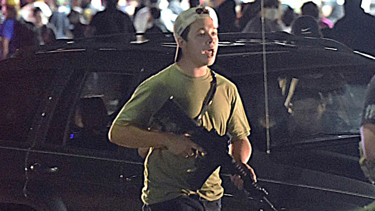 In this Tuesday, Aug. 25, 2020, file photo, Kyle Rittenhouse carries a weapon as he walks along...