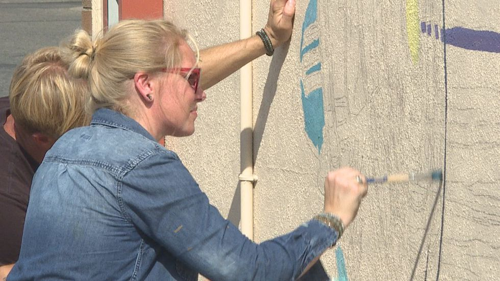 Nick and Nicole Fischer work on Aberdeen's newest mural on 6th Avenue