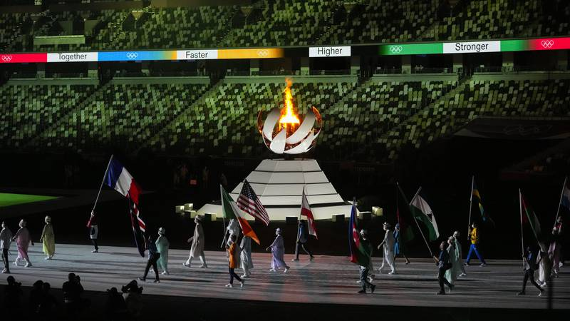 The Olympic flame burns as athletes and volunteers carry flags during the closing ceremony in...