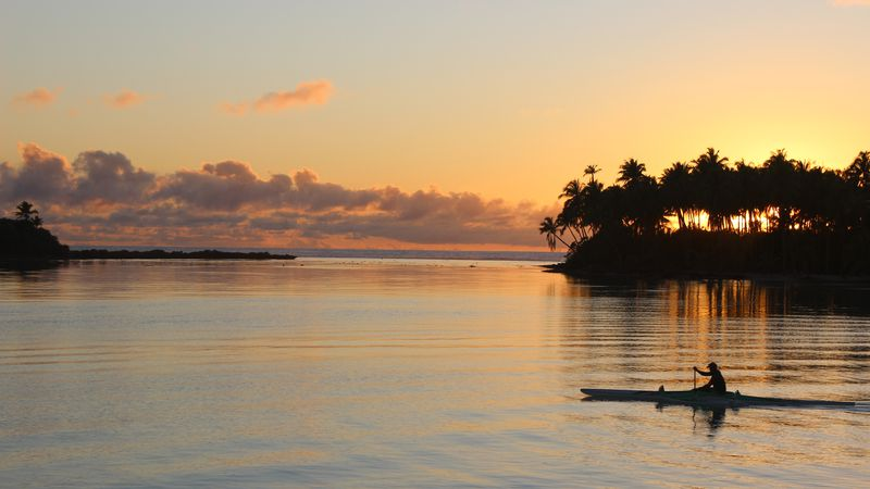 In this Oct. 30, 2015 photo, the sun rises over the lagoon in Bora Bora, as a kayaker passes...