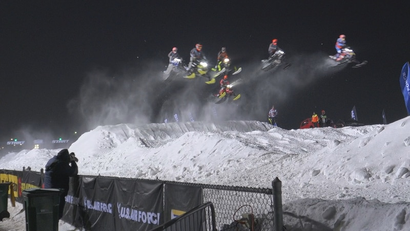 Drivers doing a jump at Sioux Falls Snocross event