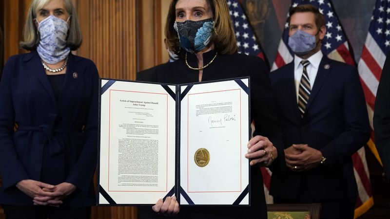 House Speaker Nancy Pelosi of Calif., displays the signed article of impeachment against...