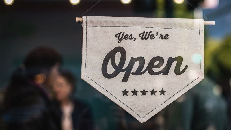 """Small business """"Yes, we're open"""" sign."""