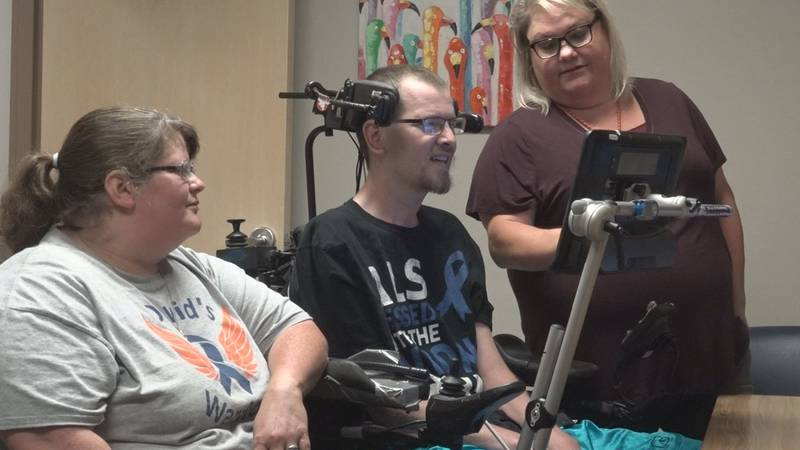 A speech-language pathologist at LifeScape helps a man diagnosed with ALS learn how to use a...