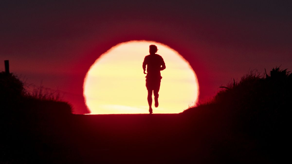 FILE - In this June 27, 2019 file photo a man runs on a small path as the sun rises in Frankfurt, Germany. The world could see average global temperatures 1.5 degrees Celsius (2.7 Fahrenheit) above the pre-industrial average for the first time in the coming five years, the U.N. weather agency said Thursday. The 1.5-C mark is a key threshold that countries have agreed to limit global warming to, if possible. Scientists say average temperatures around the world are already at least 1 C higher now than during the period from 1850-1900 because of man-made greenhouse emissions.