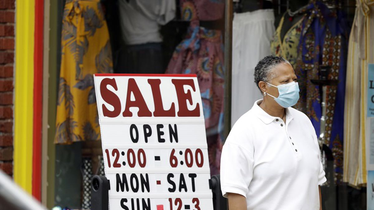 A woman walks past a boutique with a sale sign, Thursday, June 4, 2020, in Cleveland Heights,...