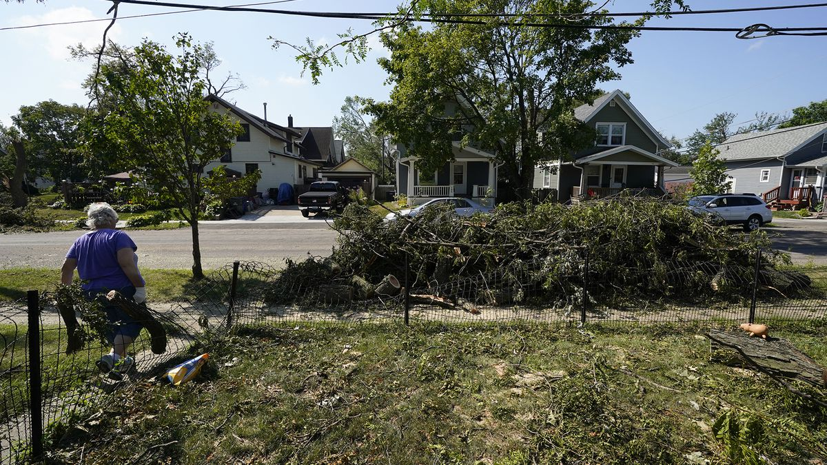 A woman hauls branches from a neighbor's yard to the street, Friday, Aug. 14, 2020, in Cedar Rapids, Iowa. Gov. Kim Reynolds pushed back Friday against criticism that she has been slow to respond to a wind storm that devastated the state and promised more help soon for tens of thousands of residents entering their fifth day without electricity.
